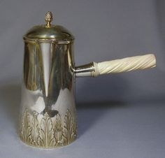 This is a gorgeous antique French sterling silver chocolate pot with a carved ivory handle. It was made by the Paris firm Gustave Keller, which was in business from 1881-1922. The pot is beautifully made with an acanthus leaf design at the base and on the lid. The piece was entirely gilded at one time, as there are the remains of gilt on the base and in the crevices.