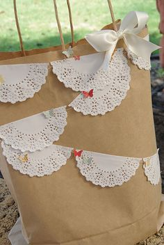 Doily Bunting -  fairy lights in between would be even better - hanging from beams on the ceiling, outside roof, bar and main table