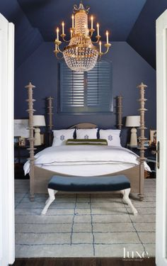 20. Chandelier A brass chandelier by Visual Comfort contrasts the deep slate blue walls and ceiling in this master bedroom.