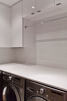 Modernist House modern laundry room The wall tile is a 12x24 polished porcelain and the counters are Caesarstone Blizzard.