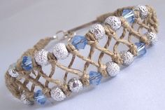 """This hemp bracelet/anklet is made using natural 20lb hemp in an """"x"""" pattern. It is accented with silver textured glass beads and light blue swarovski crystals.It has a lanyard and chain..."""