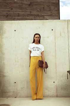 LA cool in mustard wide leg pants and a printed tee.