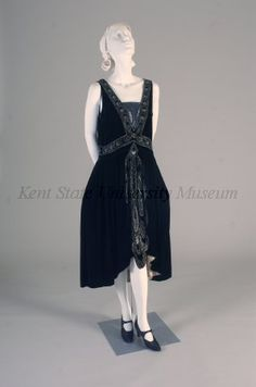 Attributed to Jeanne Lanvin Date	1928, ca.Black velvet, sleeveless, plunging V front neckline (modesty panel added), back V neckline, glass, pearl & diamante beading at neckline & above waist in banded waterfall motif, skirt with panniers, shaped hem, waterfall bead down CF, hem lined in gold lame CB 38""