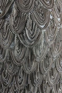 An Alexander McQueen for Givenchy chain-fringed grey crêpe de chine evening gown, Spring-Summer haute couture collection, 1998, labelled P/E 1998, no 14 and with Press Sample stamped in black, the white organza bodice with diagonal band of scale-like silver chain loops descending diagonally from the high neck across the hips, the skirt front with metal bauble buttons, long trained skirt, bust 81cm, 32in; together with an image of the gown being worn on the catwalk (2)