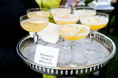Bride signature drink peach bellini in coupe glass fresh peach slices on tray cocktail hour