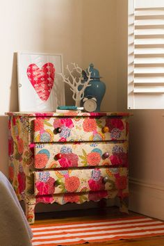 DIY floral dresser! I love this. The picture is for inspiration only, but we have so many pins on Pinterest telling us  how to modge podge that this will be a piece of cake!! Love the fabric here!