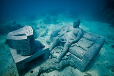 British sculptor Jason de Caires Taylor's new photos of the underwater museum in the National Marine Park of Cancun, from his installation, called The Silent Evolution. This is one of over 400 submerged sculptures. (Sharks haven't found that hamburger yet.)