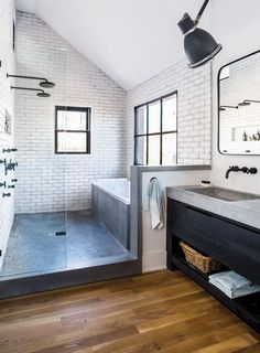 White subway tile, hardwood floor, concrete sink, black vanity, and black window trim