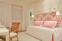 O romantismo do papel florido até a metade da parede, fazendo dupla com as capas de travesseiro rosas  Imagem casa.com