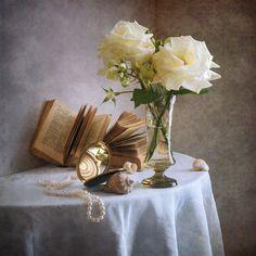 'Zwei weiße verblasste Rosen' von Nikolay Panov bei artflakes.com als Poster oder Kunstdruck $14.37 https://www.artflakes.com/de/products/zwei-weisse-verblasste-rosen Blühende Stilllebenphotographie mit kleinem Blumenstrauß der weißen wellenden Rosen im Glasvase, alte Bücher, Perlenhalskette, Weinlesespiegel mit Reflexionen und Seeshells auf weißem Drapery in der Innendekoration