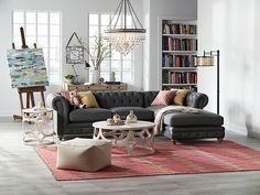 A stylish and relaxed living room with tufted gray sectional, crystal chandelier and white-washed wood coffee table.