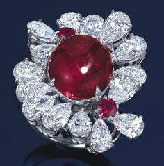 A RUBY AND DIAMOND RING  Designed as a floral cluster, centering upon a cabochon ruby weighing approximately 8.82 carats, to the pear-shaped diamond petal surround and circular-cut ruby pistils weighing approximately 0.53 carat total, mounted in platinum