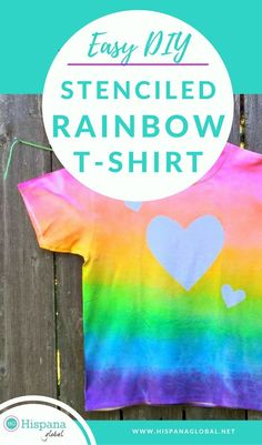 If you're looking for a simple and colorful DIY T-shirt project to make with your kids, here it is. These step by step instructions will make craft day a success. Choose your own design, pattern, and colors. This spray paint technique looks like tye dye but is easier and quick. Even teens will love this stenciled rainbow t-shirt idea and activity. You can even use this same #tutorial for a dress or tank top! Add iron on lettering for a more personalized item! #craft #ideas #tshirts #DIY…