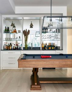 A basement wet bar boasts white cabinets paired with black quartz countertops fitted with a square bar sink and brushed nickel faucet against a mirrored backsplash lined with stacked glass shelves lined with libations.