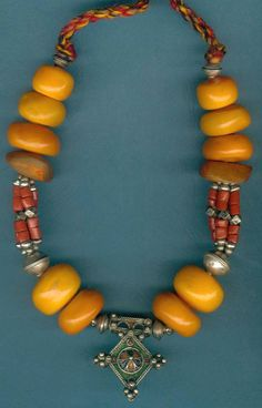 Phenolic amber, coral and Berber Silver. The design of the Croix de Sud enameled pendant denotes its origins to be from the village of Goulamine in southern Morocco.