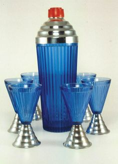 A blue ribbed Art Deco cocktail shaker with metal top, red knob, and matching…
