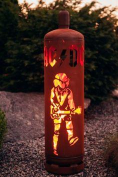Edelrost Feuersäule Gasflasche ACDC Dekorativ und ein Hingucker alleine schon wegen der ausgefallenen Form ist unsere Feuersäule Gasflasche ACDC. Ein tolles Highlight im Garten für alle Fans der Kultband ACDC, den Helden unserer Jugend. Auf der Gasflasche ist das offizielle Logo der Band sowie der Gitarrist Angus Young abgebildet. Die Gasflasche hat hinten oben eine Öffnung zum Nachschüren mit Holz, im unteren Bereich ist eine verschließbare Öffnung eingearbeitet, die ein einfaches und rasch