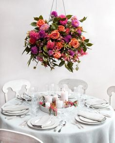 arrangements of fuchsia blooms, garden roses, dahlias, gloriosa lilies, and camellia foliage in metal baskets lined with moss and floral foam