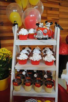 Uma escadinha recebeu os cupcakes com orelhinas e também os copinhos com mini mousses de maracujá com chocolate que foram personalizados com detalhes no tema da festa: Mickey.