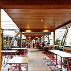 Design by Red Design Group-Extending the cafeteria into the courtyard has re-engaged the building with the outdoors. Financially the hospital also gains remodeled reception/admissions and cashier infrastructure without cost along with a revenue stream for improving front-line patient care.