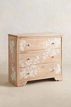 White floral design on raw wood dresser