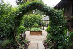 Beautiful Gracie Modern Arbor/Moon Gate with climbing roses creates an amazing gateway to a side yard herb and cutting garden in Palo Alto, CA.  TerraTrellis.com