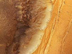 A landslide-riddled part of the Martian canyon Ius Chasma is seen in a new image by the European Space Agency's High Resolution Stereo Camera.    Spanning 584 miles (940 kilometers), Ius Chasma forms the northern boundary between the western half of an enormous valley system called Valles Marineris and the Martian highlands.    In the same process that formed Earth's East African Rift, the Martian crust split and formed the gigantic canyon system, one of the solar system's largest.