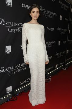 Lily Collins in an elegant white lace evening dress at the red carpet for The Mortal Instruments: City of Bones Toronto Premiere. Floor length sheath evening dress with long-sleeves and open back design. Bateau neckline.