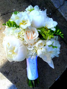 White and Mini Green Hydrangeas, White Peonies, Freesia, White Ranunculus Vendella Roses No greenery and they are bound together with a Satin Ribbon with Pearl Beading going down the center of the stems. www.flowersfromus.net