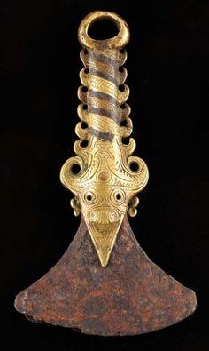 Manche de pierre à feu la lame de fer est enchâssée dans un magnifique ornement en bronze, représentant de part et d'autre une tête de Singa surmonté de symboles représentant une rangée de cornes décroissantes alliant les trois métaux. Terminé par un anneau de fixation. XIXe ou avant. Fer, cuivre et bronze Indonésie, Sumatra, Batak