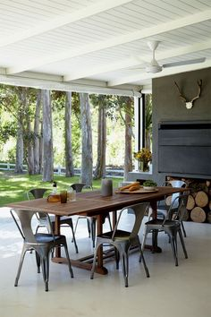 farmhouse indoor + outdoor room | modern black + white beamed ceilings | rustic table | metal chairs