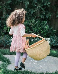 This little one is picking fresh flowers with our Natural Market Basket in hand.