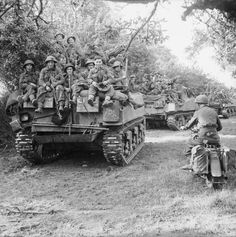 British troops riding on the back of Sherman's in Normandy. The 52 on the rear denoting that it was tanks from 1st Armoured Battalion Coldstream Guards
