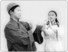 According to the Wing Chun master Yip Man, Ng Mui was Abbess at the Henan Shaolin Monastery and managed to survive its destruction by Qing forces during the reign of the Kangxi Emperor (1662–1722). She fled to the White Crane Temple. (which this account locates in the Daliang mountains between Yunnan and Sichuan)where she met a girl of fifteen named Yim Wing-Chun (Ng Mui on left; Yim on right)