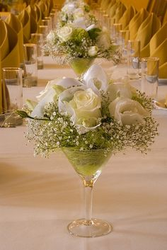 We loved this idea of gorgeous white roses in champagne glasses as centerpieces at a wedding reception. Team them with simple and elegant white table covers and shimmery gold spandex chair covers from Sculptware for beautiful results. :)