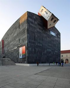 Erin Wurm and MOMAK(Museum Moderner Kunst), the largest art museum in Austria, collaborated to create some architectural buzz in 2006. The 'Attack House' was the result.  Wurm installed the house on  the outside facade of the MUMOK building and indicated that it was a symbol for an everyday occurrence as well as small-mindednes. (?)