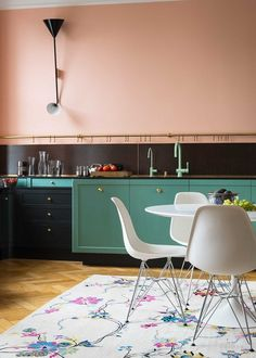 green & turquoise cabinetry, peach walls in kitchen. Hanging utility bar