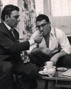 Boys: The Kray twins Reggie and Ronald light cigarettes over a cup of tea