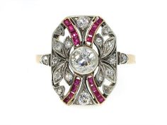 A dazzling design that is simply to die for, this antique Edwardian ruby and diamond ring will quickly become an accessory essential. A golden band is crowned by a cushion shaped cartouche of a leafy diamond set design with ribbons of rubies around a center bezel set diamond.