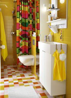 Salle de bains colorée avec un meuble lavabo blanc et un miroir, des serviettes jaunes et un rideau de douche avec un motif d'hexagones en jaune, vert, orange et rose.