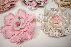 Paper Doily Flower Tutorial - includes a video on YouTube. She uses the Tim Holtz tattered florals die and martha stewart border punch(es)
