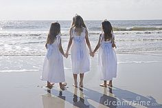 Three young girls wearing matching white dresses, looking out at the ocean at the beach