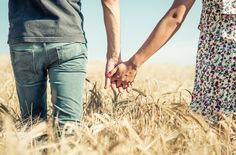 Couple holding hands in a wheat field - Couple holding hands in a wheat field. walking together in the nature