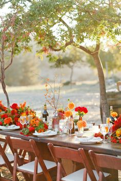 vibrant red and orange floral centerpieces in eclectic vases | photo: christinefarah.com