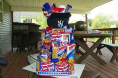 "Another Pinterest friend and I made 2 of these ""cakes"".  Theme was baseball.  Cracker Jacks, Peanuts, Pop Corn, Big League Chew Bubble Gum, Sunflower Seeds, Hat, Ball, and American Flag.   This was for a Benefit Auction for our boys school."