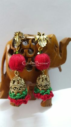 This Tribal Zumkha Earring in green and red is made from Cotton thread beads, antique base studs looks like leaf and glossed with crocheted border. You can pair it with attractive attire. #craftsofindia #indianhandicrafts #madeinindia #craftsbazaar #artsandcrafts #handmade