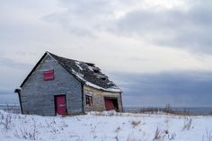 """Snow and cold are coming in through the broken window of this abandoned house, the roof and the """"garage"""" door."""