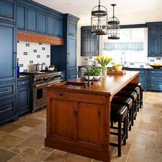 Texture rules this kitchen. The stained-wood island showcases knots and grain of the wood, adding warmth to the deep blue outer cabinets. A plank of matching wood above the range ties the room together. Kitchen Colors, Kitchen Renovation, Small Space Kitchen, Kitchen Remodel, Kitchen Design, Blue Kitchen Cabinets, Stained Kitchen Cabinets, Blue Kitchen Island, Contrasting Kitchen Island