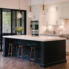 Love the white kitchen with a dark island and gold accents