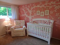 Adorable baby girl nursery & tutorial on using fabric for wall-to-wall covering instead of painting. The pink wall behind the crib is actually fabric